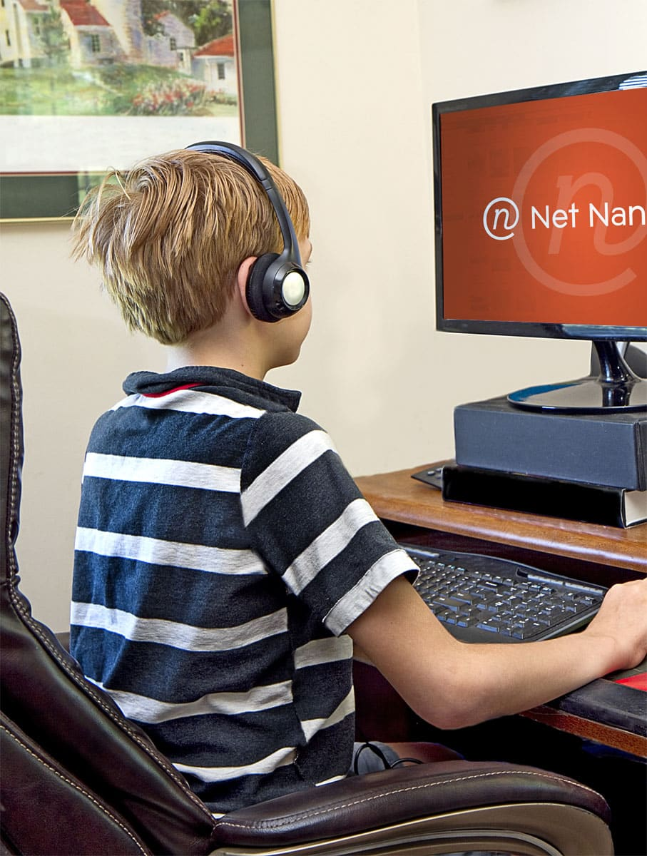 Boy wearing headphones while playing video games at computer.